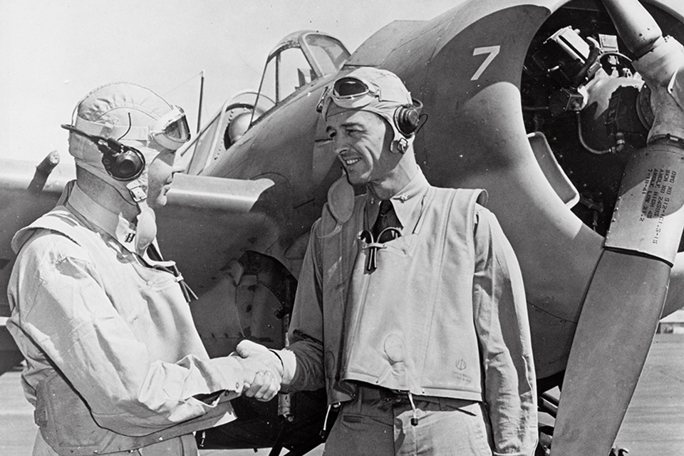 O'Hare, (left) shaks hands with his squadron commander, Lt. Cmdr. John S. Thach, in front of a Grumman F4F Wildcat at an Oahu air base after their action at Rabaul. (U.S. Navy)